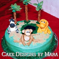 Jungle/zoo Cake  I made this cake for a 1st birthday. Iced in Buttercream, piping gel pond & gumpaste animals. The plam trees are pretzels w/ royal...