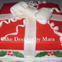 Christmas Gift  This is a yellow cake iced in buttercream covered in fondant with fondant accents. (I forgot to remove the tissue before I took the picture...