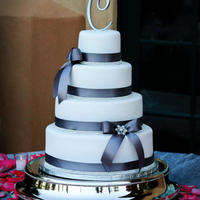Breann 4 tier white fondant covered with pearl sheen, charcoal grey ribbon, bling band, ribbon bows with bling broaches. Flavors included...