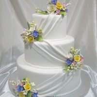 Elegance Display cake for a bridal show. Sizes 6, 9 and 12. Fondant covered with gumpaste flowers.