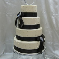 Ivory Wedding Cake This was made for a bridal show. Ivory fondant with brown satin ribbon and bling broaches. Sizes were 6, 8, 10 and 12.