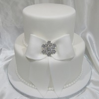 Pure Elegance Made for a bridal show. 2 tier 6 and 9 inches, fondant covered and sprayed with pearl sheen. Fondant bow and bling broach.
