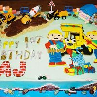 Bob The Builder Bob the Builder cake iced in buttercream. Colorflow letters and plaque. Fondant road, brick sides and letters. Candy legos, rocks and logs...