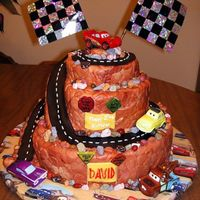 Disney Cars Cake Stacked cake covered with fondant. Fondant road, chocolate rocks and toy Disney Cars characters.