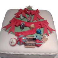 Decorated Christmas Tree Cake Fruit cake with marzipan layer finished with sugarpaste layer and decorations.