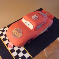 "Car Cake Baked in a race car shaped pan with some cake ""padding"" added for fenders and spoiler. Edible transfer stickers."