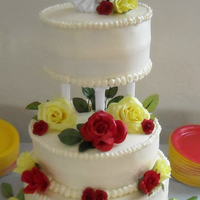 Yellow And Red Rose Wedding Cake butter cream frosting. Artificial roses