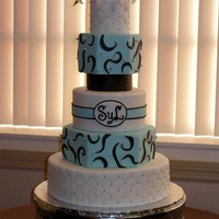 5 Tiered Light Teal & Brown Wedding Cake  This is a 4/6/8/10/14 inch, rolled fondant iced cake with a 5 inch foam spacer and live flowers. The 8 and 10 are Hexagon shaped. The cake...