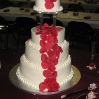 The Lester Cake Cake is iced and filled in all BC. The 3 bottom tiers are hearts the top is a round. On a clear plate with spiked pillars. Fake rose petals...