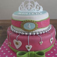 Pink Cake With Bow And Tiara Top cake filled with chocolate mousse and blackberry jelly. Bottom cake filled with strawberry mousse. Both are covered with marzipan,...