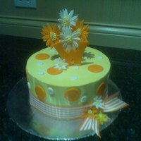 Orange And Yellow Yellow cake with orange striped ribbon and some stick daisies.