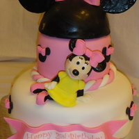 Minnie Mouse This cake is yellow with ganache filling. The head piece of the ears is cake, the ears are gumpaste. Minnie is a RKT with fondant.
