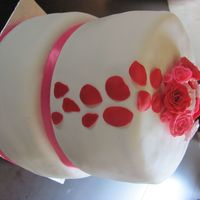 White, Pink And Roses Anniversary Cake This cake was done for a friend's Anniversary. Top layer was chocolate with buttercream, covered in Fondant. The bottom layer was...