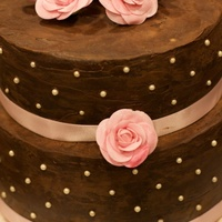 Engagement Cake Chocolate cake both covered in chocolate ganache. Draggies added with pink ribbon. Roses are made out of gumpaste.
