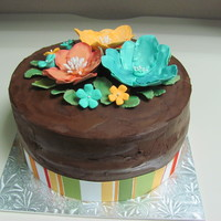 Co-Worker B-Day Cake This cake is chocolate cake, covered with chocolate ganache. All flowers are made out of fondant w/ a hint of glitter.