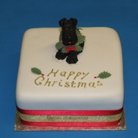 Mini Christmas Cake With Mini-Schnauzer Fondant covered mini fruit cake. Topper dog and wreath from sugar paste.