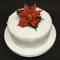 Poinsettia Christmas Cake Fondant covered fruit cake with snowflakes and poinsettia made from sugar paste.