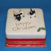 Sheep Christmas Cake Fondant covered miniature fruit cake with antler-wearing sheep toppers made from sugar paste