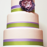 Pink Wedding Cake With Purple Gumpaste Flower Accented with green and purple grosgrain ribbons