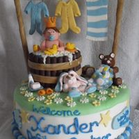 Xander's Baby Shower Cake Cake is covered in mmf with decorations made from chocolate and gumpaste. Everything is edible except the clothes line. Everyone loved it...