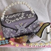 Sweet 16 Cake is covered in mmf with gumpaste and chocolate accessories. This is my first purse cake and shoe so I am very happy with the results.