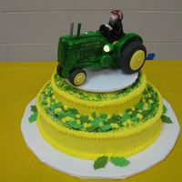 John Deere white cake with butter cream icing and fondant tractor and leaves. The tractor also had burning headlights.