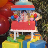 "First Birthday Took the design from the Wilton book. Fondant tiered cakes - 6"" presents and a 9"" big present"