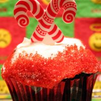 Gluten-Free Chocolate Cupcake Gluten-free chocolate cupcakes; buttercream frosting w/sprinkles and plastic candy cane topper.