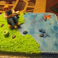 Fisherman's Birthday this is a carrot cake with cream cheese icing. fondant fisherman and fish, rocks, etc..