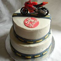 Motorcycle Birthday Cake Happy Birthday, Jay! 2 tier, chocolate fudge cake, iced in butter cream with fondant accents. Motorcycle is a toy.