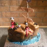 Pirate Ship Cake white sponge with strawberry jam and vanilla buttercream. Covered with White icing then painted to give a wood grain effect. This is the...