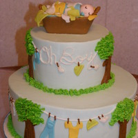 Clothes Line Cake Iced in buttercream with fondant baby clothes. Basket is made of fondant/gumpaste. TFL