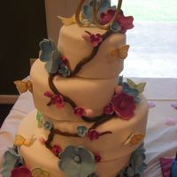 Floral Butterfly Wedding Cake Staggered French Vanilla cake with White Chocolate Buttercream under MMF. All flowers, vines, and butterflies MMF, and formed and hand...