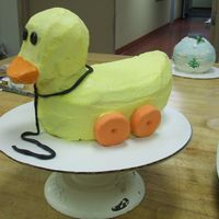 Toy Duck This is a duck that I carved out of pound cake and covered with buttercream icing, gum paste wheels, and choco-pan string