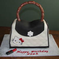 Hello Kitty Purse Cake Fondant cake with gumpaste handle. Lipstick is made of gumpaste. Made to resemble a favorite purse.