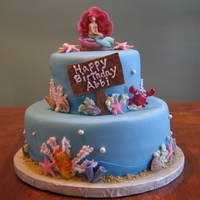 Ariel The Little Mermaid Cake 10 and 6 stacked cake covered in fondant. Shells,starfish, and sign made from sugarpaste. Made for a sweet girl who loves Ariel.