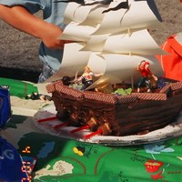 Pirate Ship With Paper Sails Ships is made with 1 round and one 9 x13. Frosting looks like planks. Made sails from wooden bbq skewers, heavy paper. Added root beer...