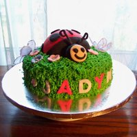 "Ladybug Torted strawberry for the 10"" base filled with strawberry buttercream. Covered in buttercream with the grass tip. Flowers are royal..."