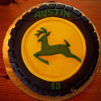 John Deere B-Day Cake  Yellow cake with lemon filling, iced in vanilla buttercream. Black fondant covers the entire cake -- the yellow hubcap and green deer are...