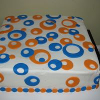 "Blue And Orange Modern Circles 12"" square cake doctored yellow mix with chocolate filling. This was a practice cake for hubby to take into work."