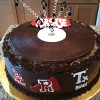 Grease Theme Cake German chocolate cake frosted in ganache. Record was made by lining a round pan with plastic wrap and then pouring wilton chocolate into it...