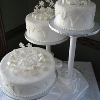 Winter Wedding buttercream iced and topped with fondant sprayed with pearl airbrush and flipped out into sanding sugar. the snowflakes are made form royal...