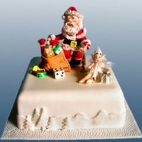 Santa's Little Helper Square Christmas cake depicting Santa with his little helper getting ready to deliver the toys