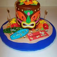 "Tiki God Luau Cake The tiki god is a 4 layer Dark Chocolate WASC cake sitting on a 5"" dummy base. Covered in vanilla cream cheese BC and chocolate..."