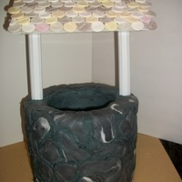 Wishing Well A dsiplay cake that was made a fund raiser. The bottom is frosted in buttercream with fondant stones/accents. The poles are cake columns....