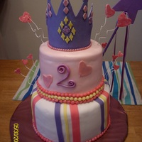 Granddaughter's 2Nd Birthday Cake Fashioned after a pinkcakebox cake. First tiered cake. Tried using rolled buttercream - never again!! Crown made from fondant.