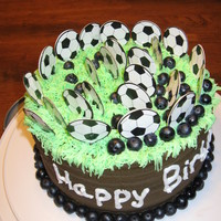 Soccer-Themed Birthday Cake  My oldest son helped make his own birthday cake. It was a soccer theme. It is vanilla cake covered in chocolate buttercream frosting with...