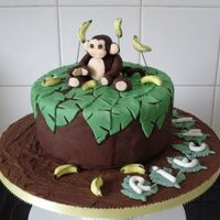 Monkey Birthday Cake Chocolate sponge Cake with chocolate buttercream filling. Covered in chocolate fondant. Leaves, monkey and bananas are made out of fondant...