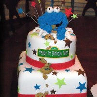 Cookie Monster Two tier cake for a little boy's 1st birthday. covered in fondant and cookie monster is rice crispy covered in frosting. Also gave a...