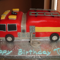 3D Firetruck French vanilla cake filled with chocolate mousse, carved and covered in red fondant, accessories in gumpaste and fondant.